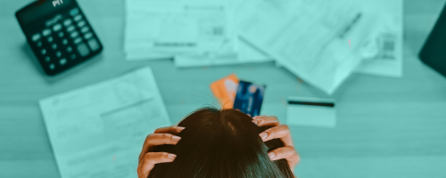 women keeping her head in hands sitting in front of documents and calculator, cyan background
