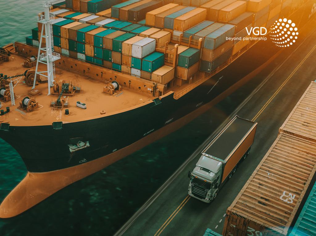 duży kontenerowiec w porcie jest w trakcie załadunku a obok stoi ciężarówka co jest symbolem opodatkowania transakcji trójstronnej