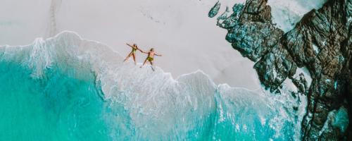 dwoje ludzi korzysta z urlopu wypoczynkowego leżąc na plaży nad niebieskim oceanem