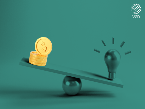 green light bulb and money on a balance scale